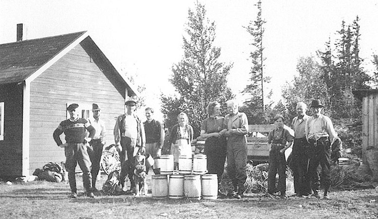 Träkaggar fyllda med hjortron. På bilden står Engström-Pelle i armkrok med okänd dam. Lanthandlaren Lars Bergqvist är andra från höger.  Foto: Privat