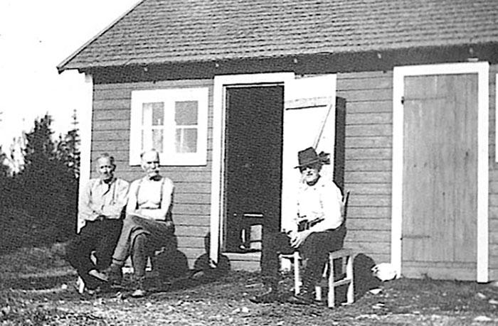Lanthandlaren Lars Bergqvist framför sin stuga som även fungerade som handelsbod, tillsammans med Engström-Pelle och okänd man.  Foto: Privat