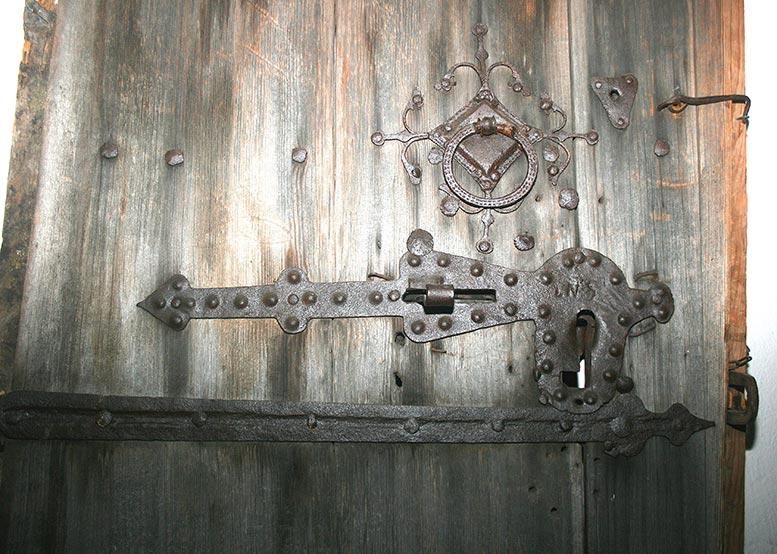 Den här kyrkporten från 1300-talet, med beslag från 1600-talet, har tjänat som dörr på ett härbre under lång tid.