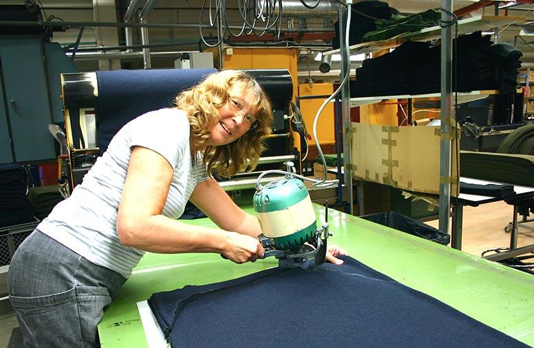 Birgitta Olsson arbetar med att stansa och sköra ut detaljer ur stora tygbitar.
