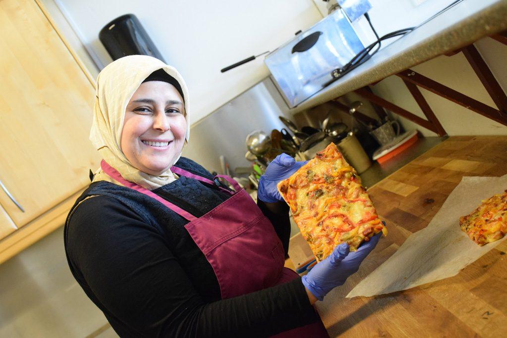 Kvinna visar en stor bit pizza.