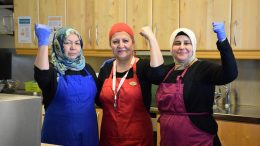 Tre leende kvinnor höjer sin knutna hand.