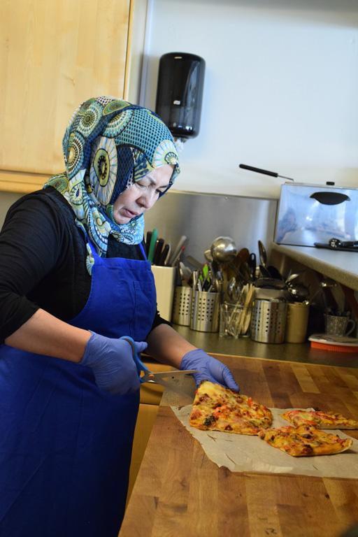 Kvinna med sax vid köksbänk.
